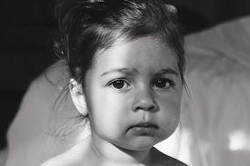 Toned Portrait of cute sad baby girl thinking.