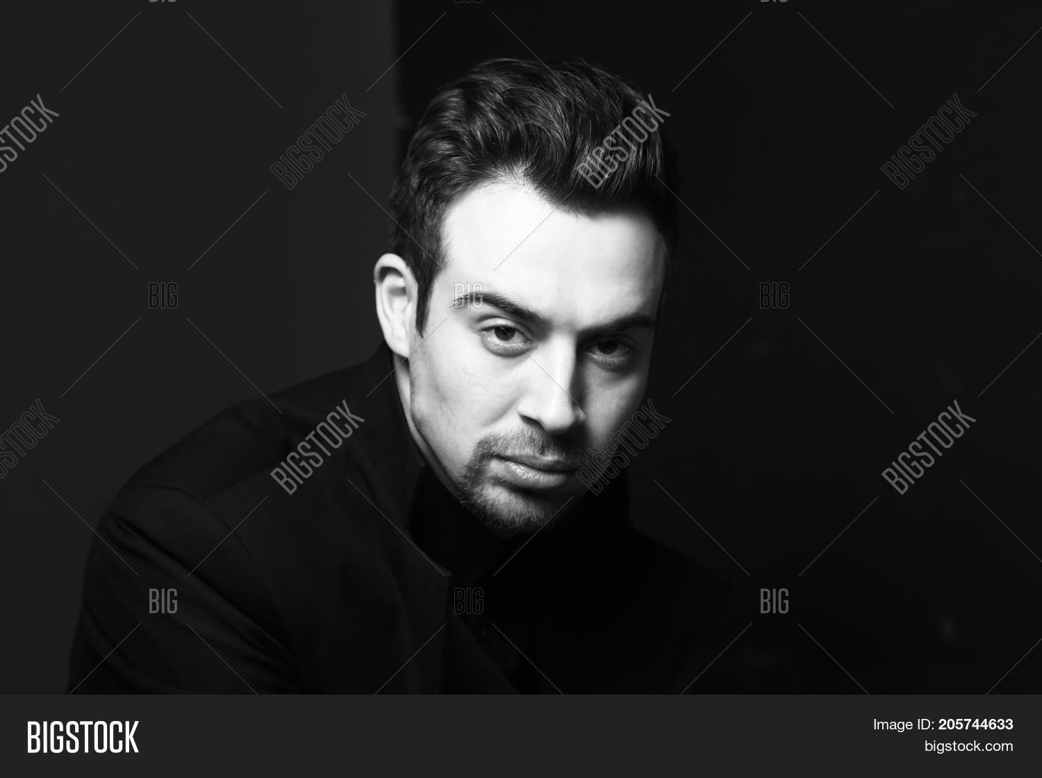 Black and white portrait of a serious young handsome man dreassed in black dramatic lighting