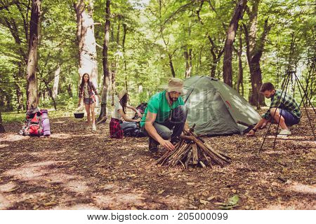Team Work. Young Bearded Male Tourist In A Hat Is Setting Campfire, Other Set On A Tent, Ladys Are U