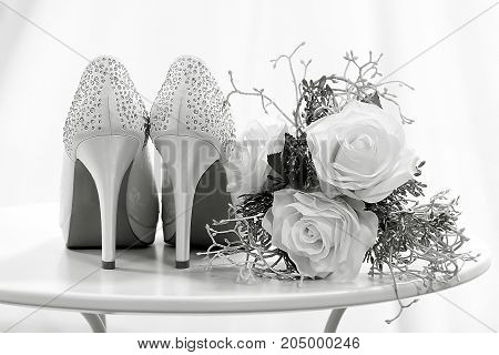 Wedding shoes and flowers on a table black and white