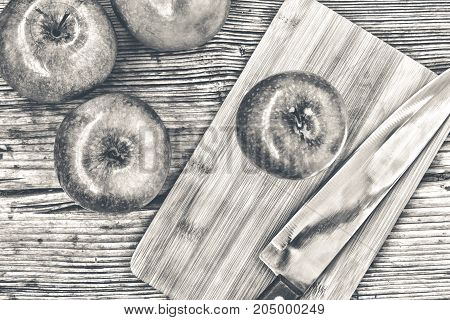 Green Apples On A Kitchen Wooden Table. Black And White Photo.