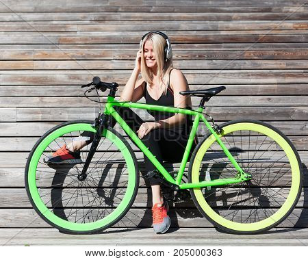 Fitness princess with long blond hair girl in black sexy outfit and sneakers resting on wooden boards with fashionable fix bike listening to music on headphones on a sunny day. Outdoor.