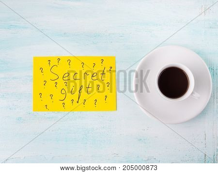 Cup of espresso coffee. Yellow card spelling words Secret gift concept flat lay