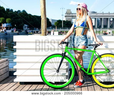 Beautiful blond girl in bikini and denim shorts posing in city park with fashionable bicycle fix. Outdoor.