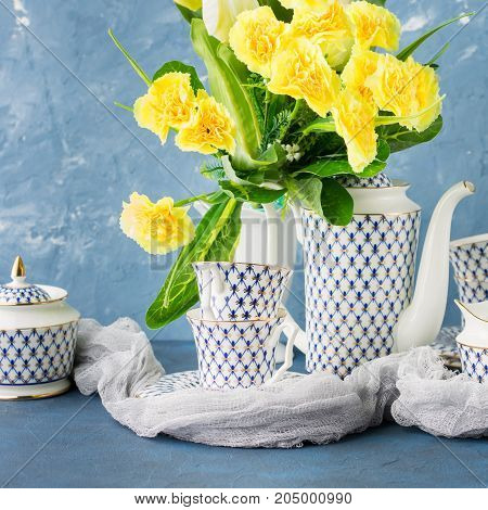 Coffee tea party china set and Easter pastel color yellow flowers on blue. Festive holiday spring background