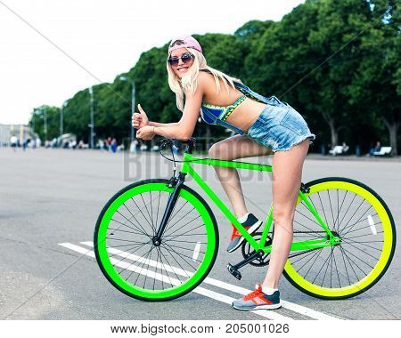 Summer in the city park. Beautiful blond girl posing on a green fashionable fix bicycle in a cool outfit. Outdoor.