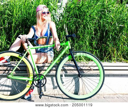 Beautiful blond girl resting on a bike ride sitting on a bench in a city park with a green fashioned fixed bike in a cool outfit. Outdoor.