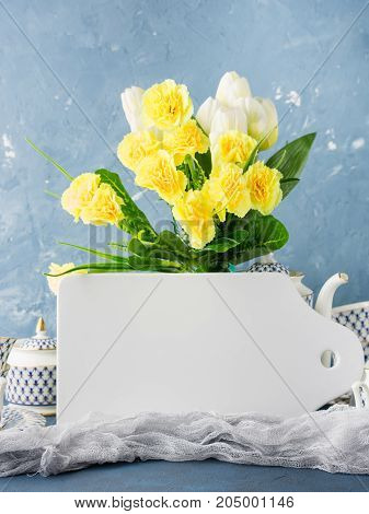White board mock up tea party set and Easter pastel color yellow flowers on blue.