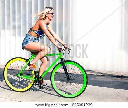 Beautiful blonde girl is riding on a steep green fixed bike in the city park of Europe. Outdoor.