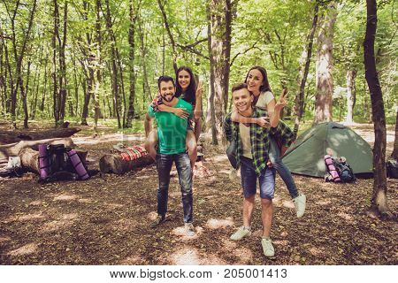 Camp In The Sunny Wood, Tent And Backpacks. Two Lovely Couples, Guys Are Piggybacking Their Girlfrie