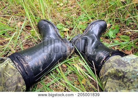Male feet in black rubber boots lie on the grass.