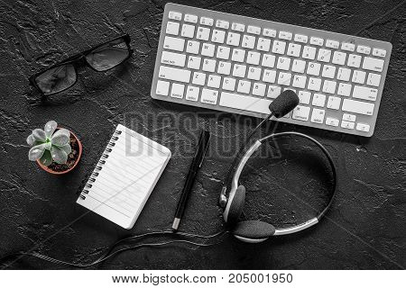Workspace at call center. Headphones and notebook near keyboard on black background top view.