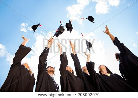 Congratulations to graduates! Low angle shot of cheerful group of six young multi ethnic graduates in black gowns throwing up their hats in the air and celebrating laughing enjoying
