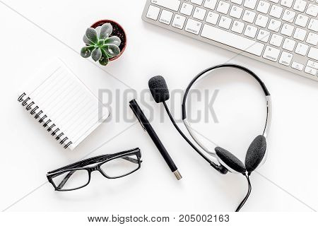 Worktable in call center. Headphones, keyboard and notebook on white background top view.