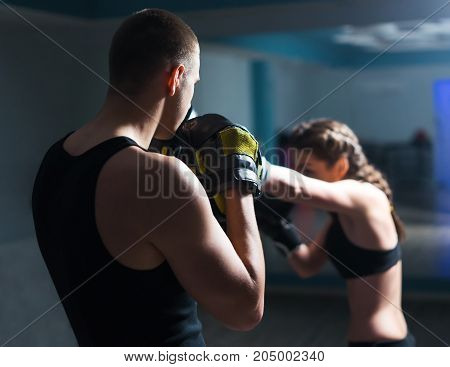 Young fighter boxer girl in training boxing and punching with personal trainer