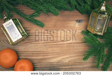 Golden christmas lantern lamps laying in fir tree branches and tangerines on burnt wooden board surface background with copy space. Christmas decorations.