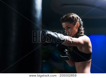 Young fighter boxer fit girl wearing boxing gloves in training with heavy punching bag.