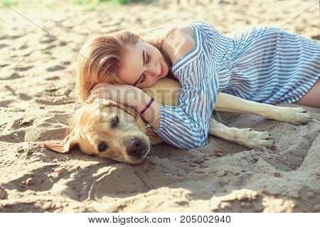 Portrait Of Young Beautiful Woman On Sand Beach Hugging Golden Retriever Dog. Girl With Dog By Sea.
