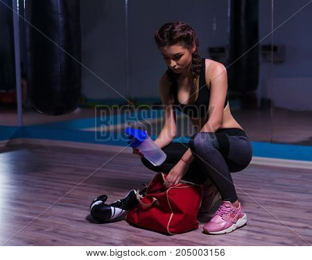 Young fighter boxer girl taking boxing gloves before training. She has water in hand