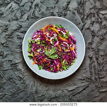 Salad healthy food. Red cabbage salad. Fresh vegetable salad with purple cabbage white cabbage salad carrot in a dark clay bowl on a black background. View from above movie effect