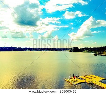 A color pop view of a boat dock on a lake with dramatic clouds.