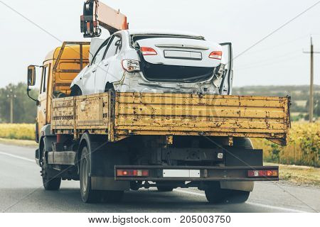 Tow truck transport smashed car after traffic accident, help on road transports wrecker broken car