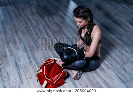 Young fighter boxer girl wearing boxing gloves before  training.