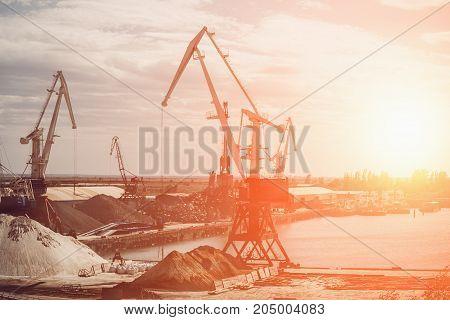 Gantry cranes, industrial landscape at sunset, toned
