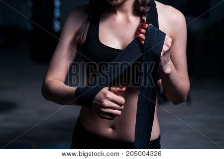 Young fighter boxer girl putting on hand bandage before training with heavy punching bag.