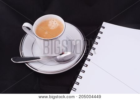 A Cup Of Coffee With Coffee Capsule And Notepad.