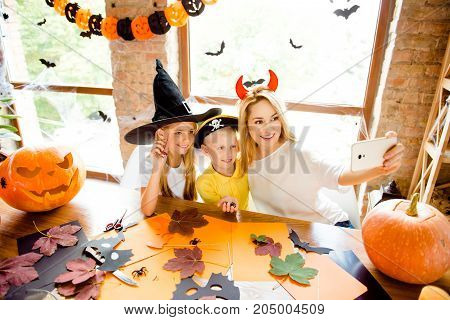 Shot Portrait Of Three At Halloween Party, Mommy And Her Cheerful Kids - Blond Small Witch And Pirat