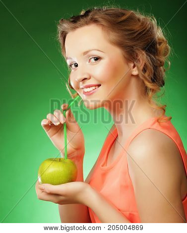 Happy smiling woman with apple and Straws Cocktail, over green background