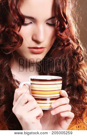 young pretty curly woman drinking coffee over beige background