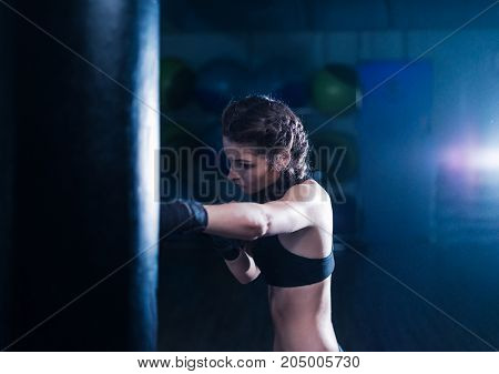 Young fighter boxer fit girl wearing boxing gloves in training with heavy punching bag. Low key image