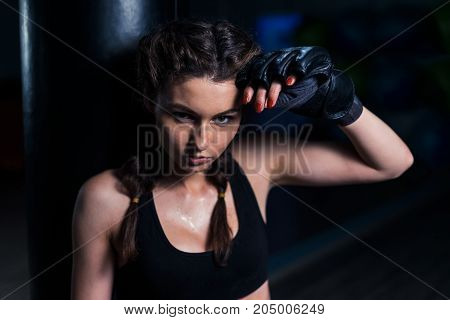 Young fighter boxer fit girl wearing boxing gloves tired after training with heavy punching bag in gym. Low key image. Woman power