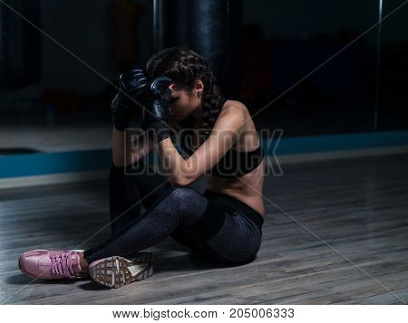 Upset young fighter boxer girl wearing boxing gloves siting on the floor after loosing fight