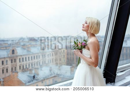 Beautiful young girl bride in a white dress standing in hotel room and looking out the window with a slight smile