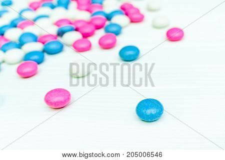 Top left frame of colored chocolate coated candy. Isolated on white background
