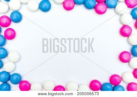 Top view of round frame made of colored chocolate coated candy. Isolated on white background. Copy space