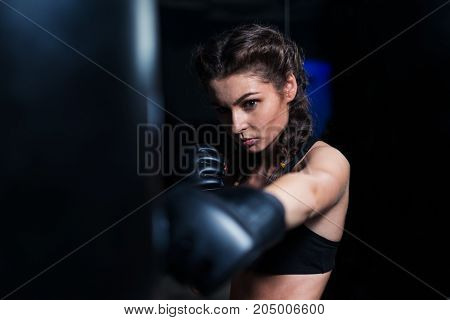Young fighter boxer fit girl wearing boxing gloves in training with heavy punching bag in gym. Low key image. Woman power