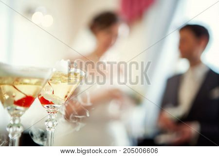glasses of champigne against the background of the bride and groom. Wedding concept