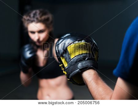 Young fighter boxer fit girl wearing boxing gloves in training  with  personal trainerin gym. Low key selective focus image. Woman power