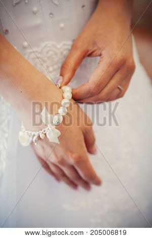 Bridal preparation, bride putting on jewelry, focus on bracelet
