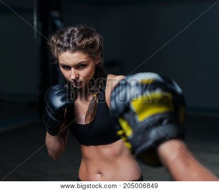 Young fighter boxer fit girl wearing boxing gloves in training  with  personal trainerin gym. Low key image. Woman power
