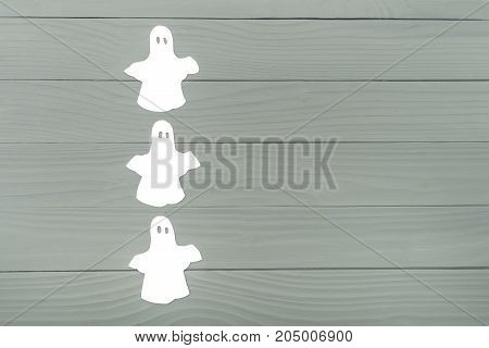 Left side of paper silhouette of three white ghosts on grey wooden background. Halloween holiday background. Copy space
