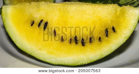 A Slice Of A Yellow Watermelon Lies On A Plate
