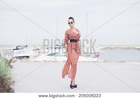 Young fashionable brunette woman wearing long dress in sunglasses posing near sea on pier with yachts