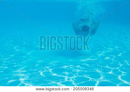 The young man dived into the pool and swam under the water