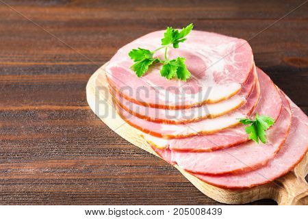 Sliced Ham With Fresh Green Lettuce Leaves On A Round Cutting Board. Meat Products On A Brown Wooden