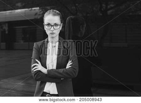 Serious blonde girl in suit boss business woman teacher or student on dark background black and white
